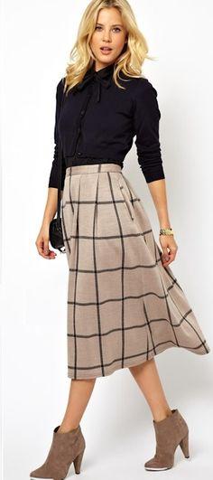 La jupe midi : pour un look preppy chic et élégant. Ci-dessus parée de motifs carreaux, l'imprimé de l'automne-hiver, à porter avec une chemise ou une blouse et des boots en daim à talons.