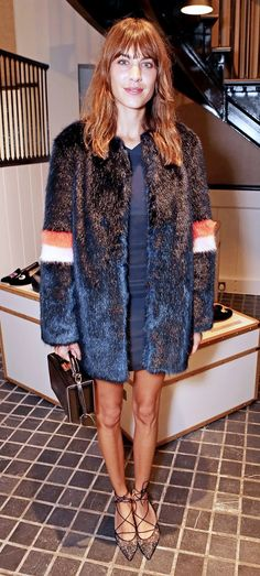 Alexa Chung wears a fur coat with a simple navy dress and Bionda Castana lace pumps.