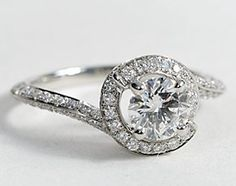 Elegant and unique, this diamond engagement ring in platinum is flawlessly crafted with a knife-edge profile that is designed with two floating spirals of pavé-set diamonds to embellish your center diamond.