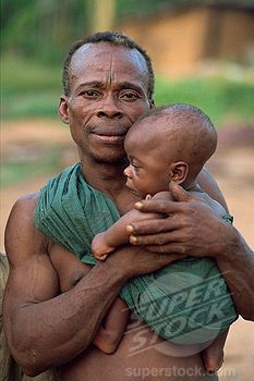 Africa | A Pygmy man holding his very young child. South east region of Cameroon. | © Robert Harding.