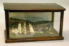 Antique Nautical Ships Diorama ships at port c1880. Seaside village featuring house, a church, lighthouse, sailboats, a steamship, and mountains in the background. antique diorama measures 10 and one half inches wide by 5 and one half inches high by 6 inches deep.