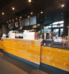 The Starbucks store in the Barclays Center Brooklyn Nets arena incorporates reclaimed basketball flooring as the primary material in the store, which makes up the feature wall, bar cladding material, wood seating element, and custom lighting.
