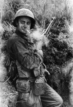 American soldier Terry Moore of F Company 184th Regiment 7th Infantry Division leans against an embankment a cigarette in his mouth and his Browning automatic rifle, Okinawa, Japan, May 1945