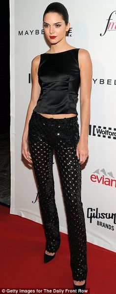 Holey moly: Kendall Jenner sported trousers that were covered in circular cut-outs, as well as a crop top