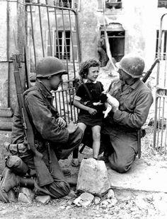 Dos soldados estadounidenses tratan de consolar a una niña herida con un cachorro. [Segunda Guerra Mundial, 1944].