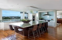 Modern kitchen with unexpected light fixture over the island in a home in Honolulu, HI designed by Peter Vincent Architects