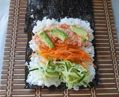 Vegetables stacked on top rice in a seaweed roll