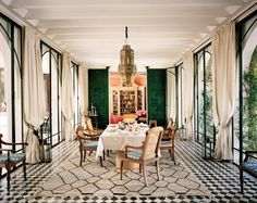 A charcoal and cream Moroccan geometric rug provides relief from the optic black and white tile floor and complements an Art Deco Oak dining table and emerald green Moroccan doors in India Jane Birley's home in Morocco.
