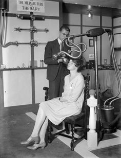 A man and a woman demonstrating medical equipment at a X-ray exhibition, beside a sign reading 'The Metalix Tube for Therapy,' 1928.