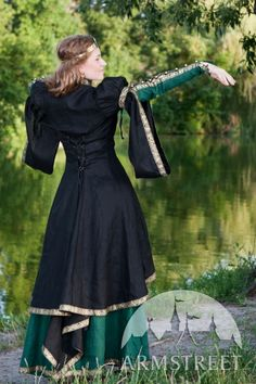 Black and gold Medieval Fantasy Overcoat. Shown over a green dress. By Armstreet.