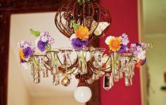 Nos recipientes de vidro, originalmente porta-velas, foram colocados lisiantos, gérberas, campânulas e goivos