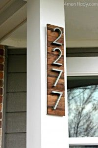 Metal house numbers on stained wood