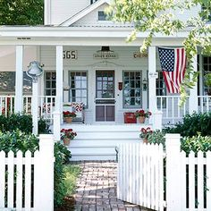 Love the porch, dinner bell, white picket fence and Old Glory!!!