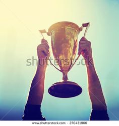 a man holding up a gold trophy cup as a winner in a competition toned with a retro vintage instagram filter effect app or action (backlit with the sun)