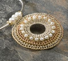 Crochet pendant with yellow gold, silver, white pearls.
