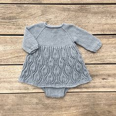 Tiny Tulips is a special one-piece for baby girls: a three-quarter-length sleeve romper with simple-cable hem and cuffs, and a full lace skirt with a pattern inspired of springtime budding tulips.