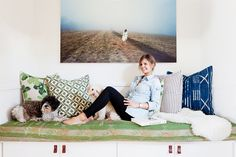 a built-in love seat with gorgeous pillows and oversized photograph