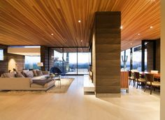 Open Plan Living Area With Wall Mounted TV Modern Glass Fireplace On Rammed Earth Walls As Room Devider Also Limestone Floor And Douglass Fir Wood Ceiling: Single Storey Hillside Residence in Paradise Valley, Arizona
