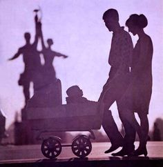 A young married couple walking with their baby past the All-Russian Exhibition Center in Moscow, 1980s.
