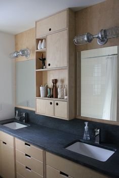 "Plywood bathroom cabinets - ""At the last minute we decided to add the plywood panels behind the mirrors. The idea initially came about because one of the lights had to be moved slightly, and we were going to need to have the drywall patched. I think this is a much more interesting solution, and I love how it ties the mirrors and lights into what looks like one big unit."""