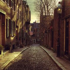 WALL MURAL INFO: Put the proud colours of Boston on your walls with the Beacon Hill, Boston wall mural. This beautiful image of a vintage street in Boston, complete with the proud american flag, shows a nice cobble stone pathway that adds depth to any room in the house. PRODUCT INFO: - Material: Peel & Stick Thin Canvas - Finish: Matte - Thickness:6.0 mil No extra tools, glue, paste or water needed for hanging. This wall mural is removable, re-usable and will not damage your walls. RETUR...
