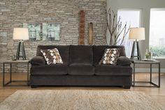 This ultra-plush Ashley Furniture sofa is the perfect place to sit-back and enjoy your home after a busy day. With its rich charcoal-hue, clean lines, and laid-back feel, this sofa is sure to create a warm and inviting ambiance in your contemporary living room.
