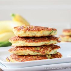 Stacked low carb zucchini fritters on a white plate with yellow squash behind.