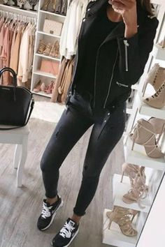 women wearing a chic fall outfit with black nikes gray skinny jeans and a black motorcycle jacket and a Givenchy bag