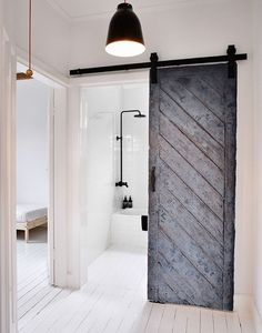 Reused old barn door creates a fabulous entrance for the Scandinavian bathroom