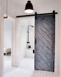 Reused old barn door creates a fabulous entrance for the Scandinavian bathroom