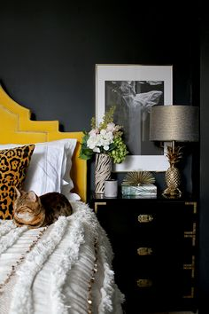 black bedroom with yellow velvet headboard leopard print cushions and gold pineapple lamp. The coverlet is a modern version of the chenille bedspread :)