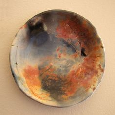 """""""Galactic Flower"""" by Cecily Smith Maples.  This hand-built porcelain plate was saw dust fired at the HDJ Clay Studio, LHUCA. It did not make it out of the firing in one piece so it was glued back together. (Broken re-glued lines fascinate me. They make me think of antiquities and museum pieces etc.)  It was made in 2009 at the HDJ Clay Studio, LHUCA."""