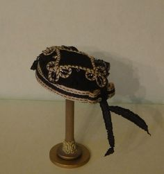 We made this hat using vintage black wool felt.  It is decorated with an antique soutache medallion that has jet beads woven into the design.  The hat