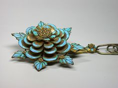 Kingfisher feathers Chinese hairpinAsia, China, Late Qing DynastyWidth : 2 1/8 inchHeight : 7 ¼ inchDepth : 6/8 inchGorgeous Chinese hairpin covered with kingfisher feathers on 4 levels of petals and one of leaves. Mounted on tremblant on gilt metal.