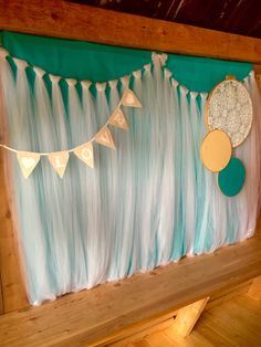 Diy photobooth backdrop using a fabric teal tablecloth, white tulle knotted on a rope, a banner, and fabric and embroidery hoops! Tuck the tulle and tablecloth up under itself and staple to wall