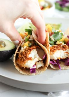 Crunchy Coconut Fish Tacos topped with a fresh mango salsa are the perfect tacos for a Cinco de Mayo fiesta or any time of year! They're baked, not fried, so you can indulge healthfully.   via livelytable.com