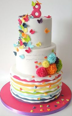 Rainbow cake with butterflies and pom poms