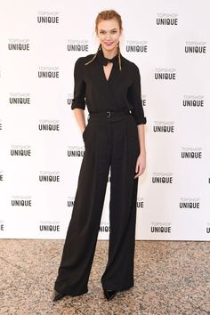Karlie Kloss keeping it cool in a black blouse and wide leg trousers with braided pigtails