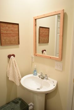 Modern, DIY Hand-Framed Mirror. Upcycle your boring bathroom mirror by adding a rustic wood frame.