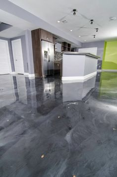 Epoxy covers the concrete floors for a glossy modern and functional look by TriCrest Homes, LLC