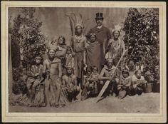 Groepsportret van Benedenlandse Surinaamse Indianen, mannen, vrouwen en kinderen en een Europese man