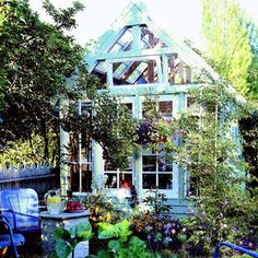 Recycled windows makes a unique potting shed! Although the structure here was designed around the window's dimensions, you could achieve the same look by adapting the idea to an existing structure. The result is a low-cost, roomy potting shed that doubles as a greenhouse and has the look of an old-fashioned conservatory. Surrounded by a white picket fence, this garden oozes charm.