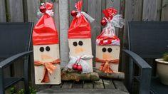 Kerstmannen blok hout met daarop een muts gemaakt van een plasticzak zodat ze buiten kunnen staan.