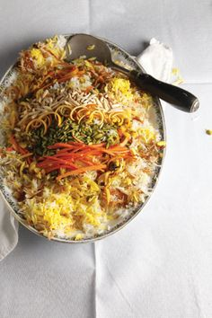 Iranian Rice Pilaf (Shirin Polow) | Saveur l (White rice transformed, with saffron,  candied orange peel, almonds, and pistachios.)