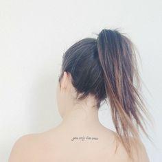 """Pequeño tatuaje que dice 'you only live once', frase en inglés que significa """"sólo se vive una vez"""", en la espalda de on Úrsula Campos."""