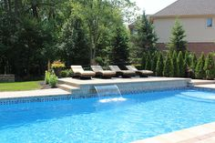rectangular pool with raised tanning deck on far side, waterfall