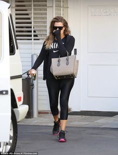 Gym chic: The brunette beauty sported head-to-toe black, including shiny leggings, a jacke...