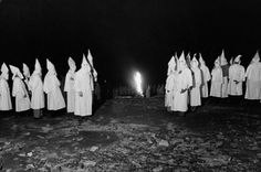 White-sheeted Ku Klux Klan members stand by a burning cross, May 1946. This Stone Mountain, Ga., ceremony was put off many times, Klansmen allegedly said, because of wartime sheet shortages during WWII.