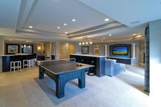 This contemporary basement living room is open and bright, with plenty of space for entertainment. The snack ledge helps separate the game room from the living space in a pleasant and subtle way.