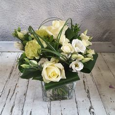 A #floral #cubevase #arrangement in white #Roses, #Lisianthus and #Carnations with looped grasses and leaves. Vase Arrangements, Grasses, Carnations, White Roses, Corporate Events, Floral Design, Leaves, Seasons, Flowers
